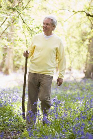 oap: Man walking outdoors with walking stick smiling