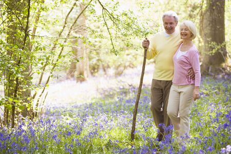 guy with walking stick: Couple walking outdoors with walking stick smiling