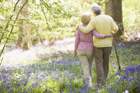 Couple walking outdoors with walking stick photo