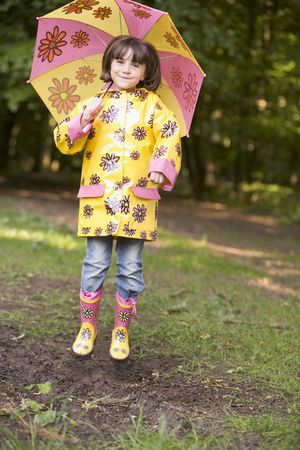 raincoat: Young girl outdoors with umbrella jumping and smiling