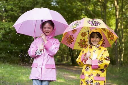 Two sisters outdoors in rain with umbrellas smiling photo