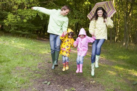 Family outdoors skipping with umbrella smiling photo