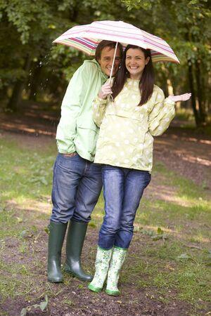 botas de lluvia: Pareja al aire libre en la lluvia con paraguas sonriente