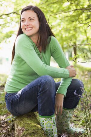 Woman outdoors in woods sitting on log smiling photo