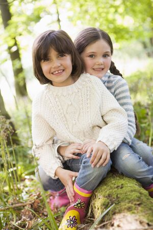 Two sisters outdoors in woods sitting on log smiling photo