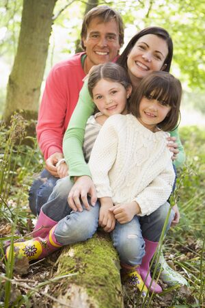 wellies: Family outdoors in woods sitting on log smiling Stock Photo