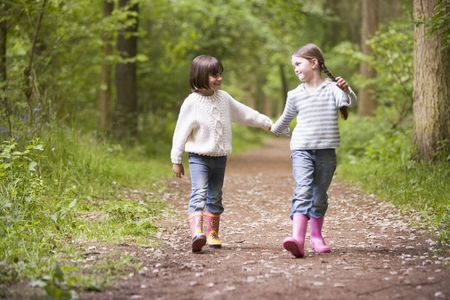 Two sisters walking on path holding hands smiling photo