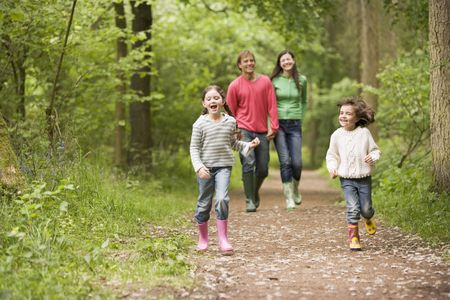 jungle girl: Family walking on path holding hands smiling