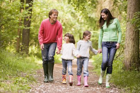 springtime: Family walking on path holding hands smiling