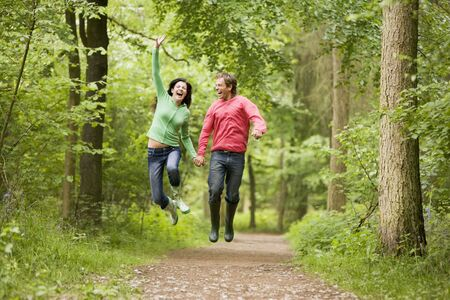 wellies: Couple jumping on path holding hands and smiling