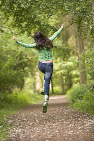 wellies: Woman jumping on path