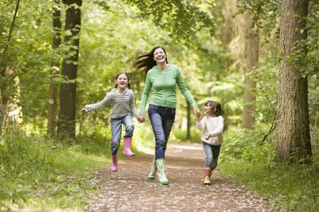 Mother and daughters skipping on path smiling photo