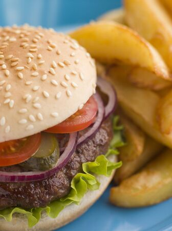 Beefburger with Salad and Pickles in a Sesame Seed Bun with Chips photo