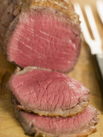uk cuisine: Roast Topside of British Beef carved on a Chopping Board