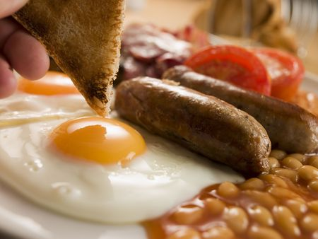 english breakfast: Dipping Toast into a Fried Egg on a Full English Breakfast