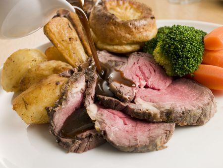 Jus wordt gegoten op een plaat van gebraden rundvlees en Yorkshire Pudding