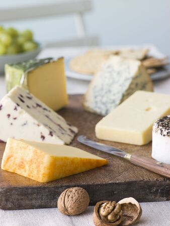 cheese knife: Selection of British Cheeses with Walnuts Biscuits and Grapes Stock Photo