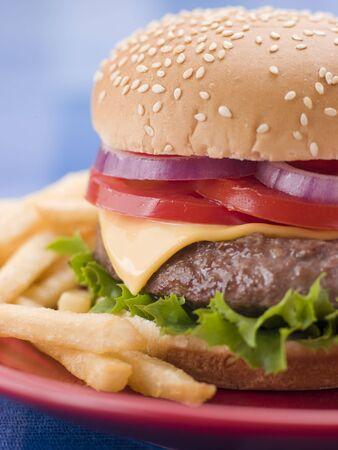 ajonjol�: Hamburguesa con queso en un panecillo de s�samo con Fries  Foto de archivo