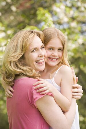 Mother holding daughter outdoors smiling Stock Photo - 3600187