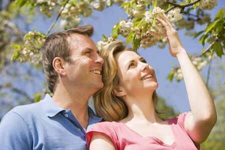 Couple standing outdoors holding blossom smiling photo