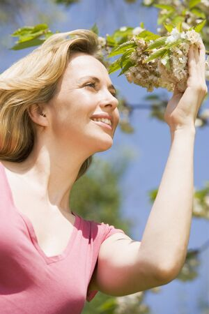Woman standing outdoors holding blossom smiling photo