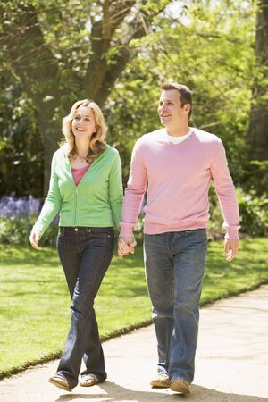 couple holding hands: Couple walking on path holding hands smiling