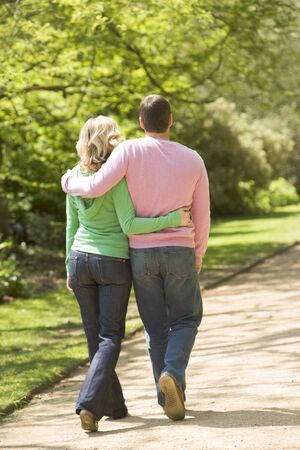 countryside loving: Couple walking on path arm in arm Stock Photo