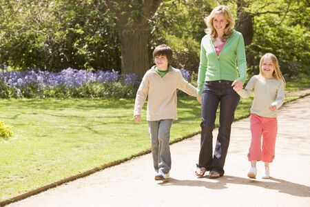 ni�os caminando: Madre y dos ni�os peque�os en la ruta para caminar tomados de la mano sonriendo Foto de archivo