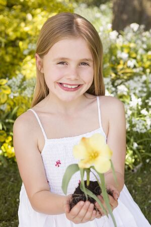 Young girl outdoors holding flower smiling photo