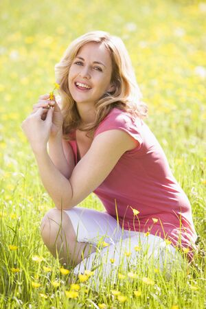 buttercups: Woman outdoors holding flower smiling