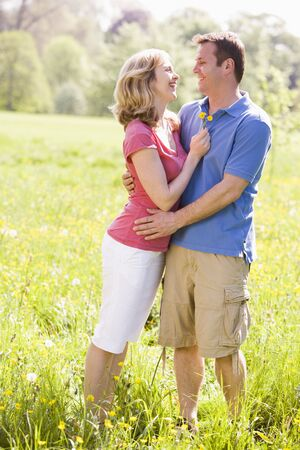 countryside loving: Couple embracing outdoors holding flower smiling Stock Photo