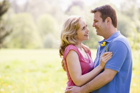 Couple embracing outdoors holding flower smiling photo