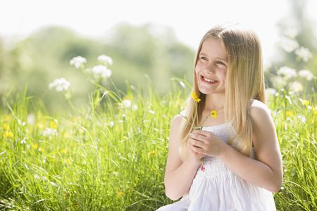Young girl sitting outdoors holding flower smiling Stock Photo - 3476577