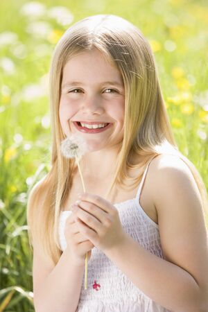 Young girl sitting outdoors holding dandelion head smiling photo