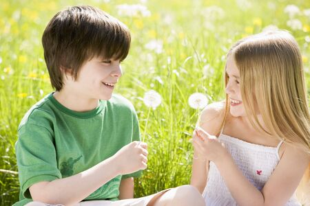 Two young children sitting outdoors holding dandelion heads smiling photo