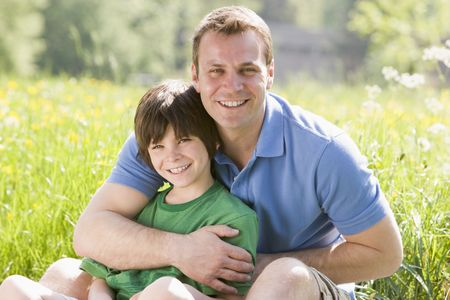 Father and son sitting outdoors smiling Stock Photo - 3476709