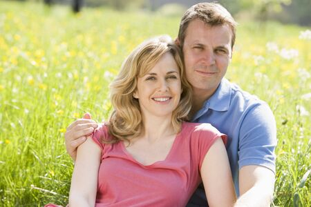 30s adult: Couple sitting outdoors smiling