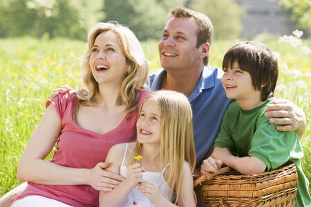Family sitting outdoors with picnic basket smiling Stock Photo - 3476792