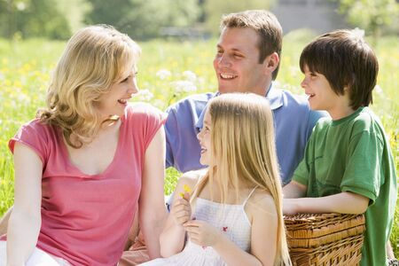 Family sitting outdoors with picnic basket smiling photo