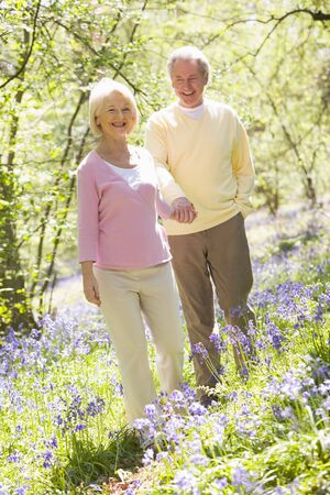 Couple walking outdoors holding hands smiling photo