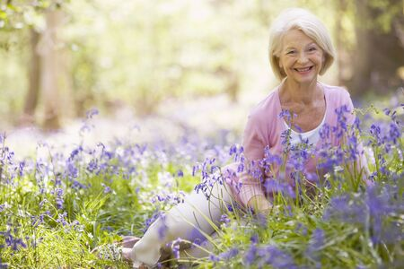 oap: Woman sitting outdoors with flowers smiling Stock Photo