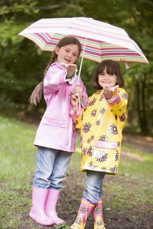 Two sisters outdoors in rain with umbrella smiling photo