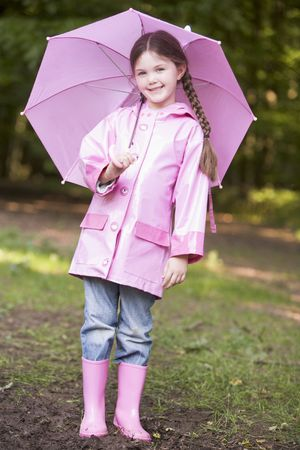 wellies: Young girl outdoors with umbrella smiling