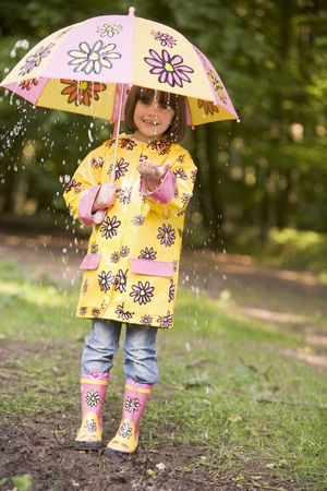 raincoat: Young girl outdoors in rain with umbrella smiling Stock Photo
