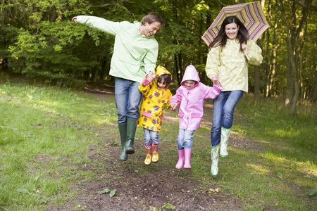 Family outdoors skipping with umbrella smiling Stock Photo - 3477302