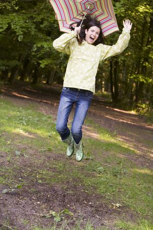 Woman outdoors jumping with umbrella smiling photo