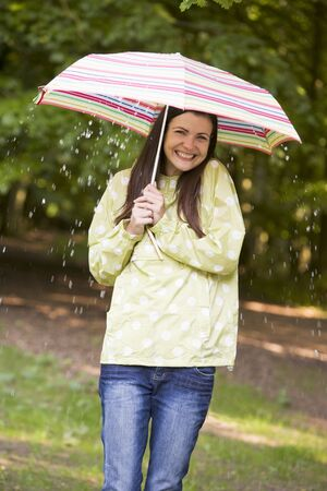 Woman outdoors in rain with umbrella smiling photo