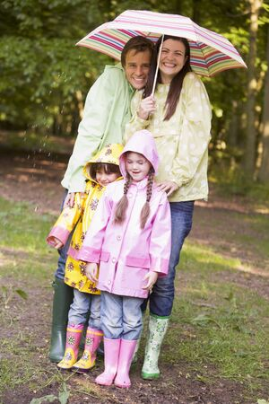 wellies: Family outdoors in rain with umbrella smiling