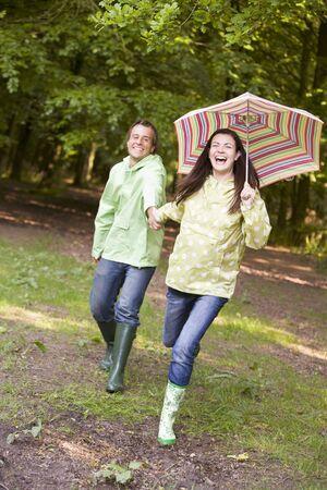 botas de lluvia: Mayor al aire libre, corriendo con paraguas sonriente Foto de archivo