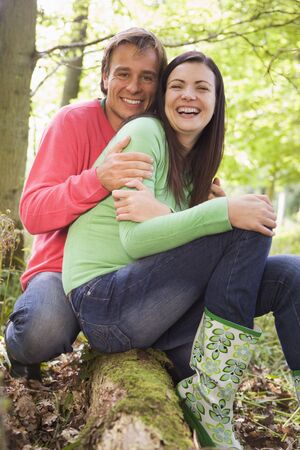 Couple outdoors in woods sitting on log smiling photo